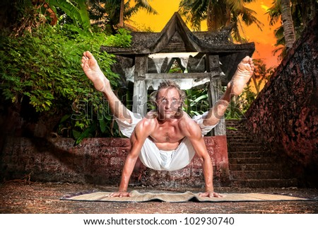 Yoga titibhasana firefly pose by fit man in white trousers near stone temple at sunset background in tropical forest - stock photo