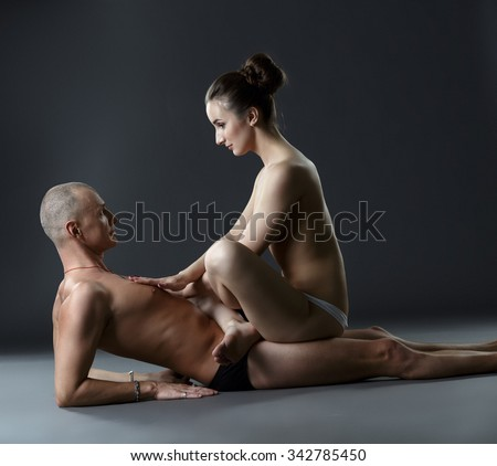 Yoga. Topless woman sits on man in lotus posture - stock photo