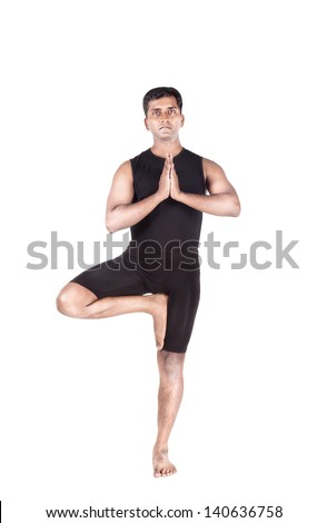 Yoga tree pose by Indian man in black costume mudra isolated at white background - stock photo