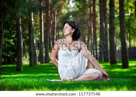 Yoga twisting pose by woman in white costume on green grass in the park around pine trees - stock photo