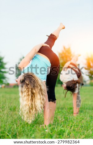 Yoga. Two young women doing yoga exercise outdoor