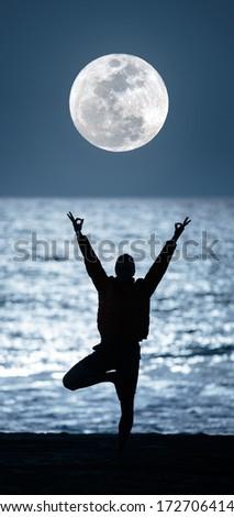 Yoga under full moon over night ocean beach. - stock photo
