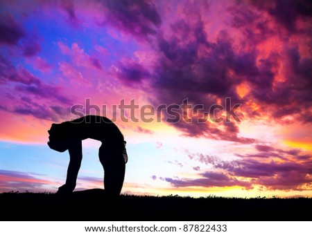 Yoga ushtrasana camel pose by man silhouette with purple dramatic sunset sky background. Free space for text and can be used as template for web-site - stock photo