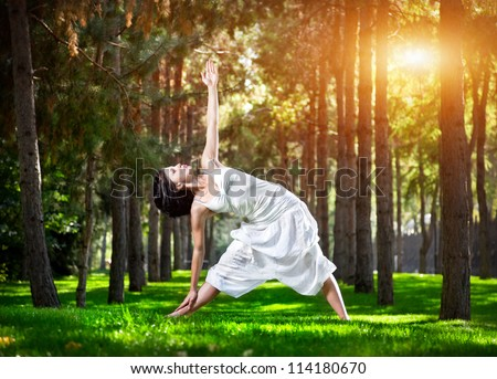 Yoga utthita trikonasana triangle pose by woman in white costume on green grass in the park around pine trees - stock photo