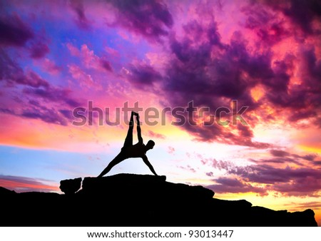 Yoga Vasisthasana plank balancing pose by Man in silhouette on the rock outdoors at mountains and cloudy sky background - stock photo