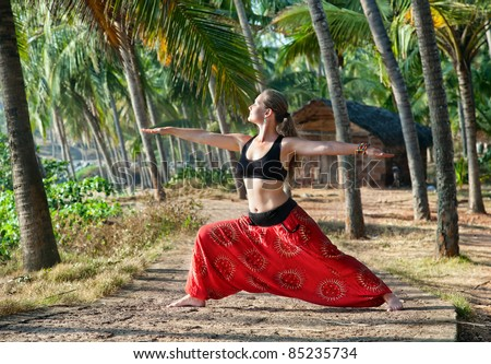 Yoga virabhadrasana II warrior pose by beautiful Caucasian woman in red Indian trousers with symbol om on the road in palm tree forest with house at background in India, Kerala, Varkala - stock photo