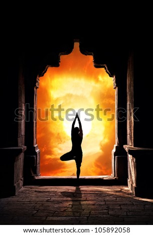 Yoga vrikshasana tree pose by man silhouette in old temple arch at dramatic sunset sky background. Free space for text - stock photo
