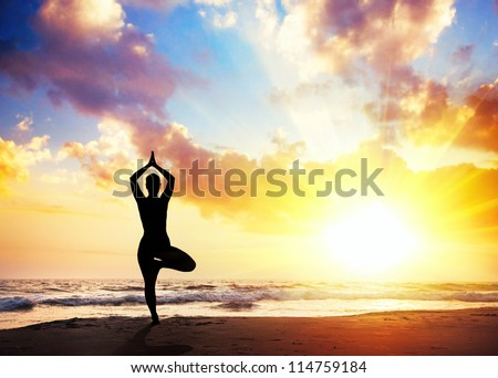 Yoga vrikshasana tree pose by woman in silhouette with sunset sky background. Free space for text - stock photo