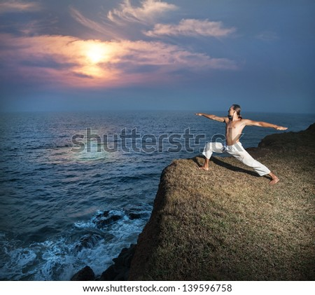 Yoga warrior pose by man in white trousers on the cliff near the ocean in Kerala, India - stock photo