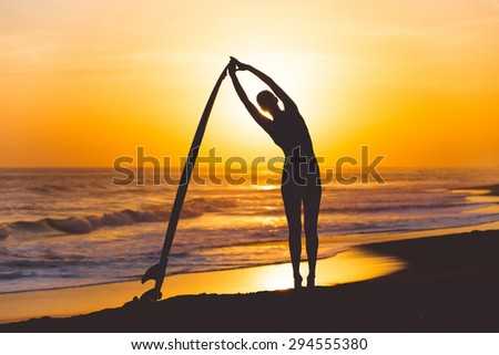 Yoga with surfboard on the ocean beach at sunset - stock photo