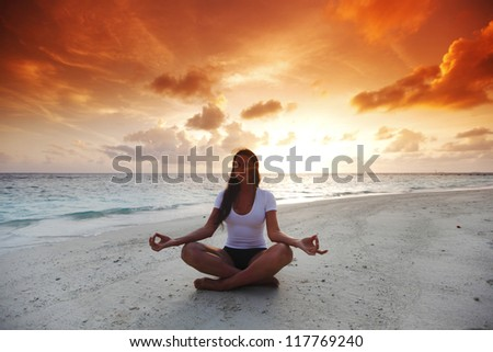 Yoga woman in lotus pose on beach at sunset - stock photo