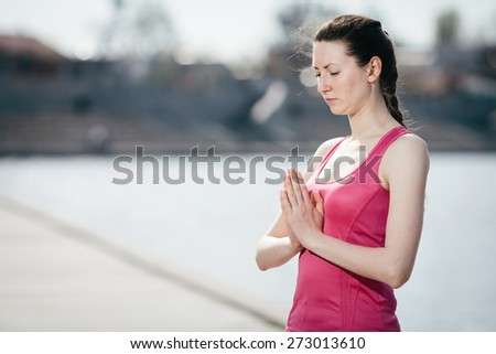 Yoga woman in the park near river - stock photo