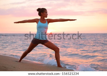 Yoga woman in zen meditating in warrior pose relaxing outside by beach at sunrise or sunset. Female yoga instructor working out training in serene ocean landscape. Big Island, Hawaii, USA. - stock photo