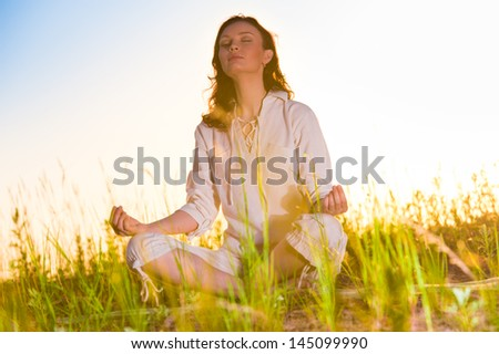 Yoga woman meditating on green grass against the sun - stock photo