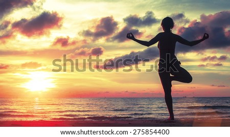 Yoga woman meditating on the beach during sunset (sunset blood colors)  - stock photo