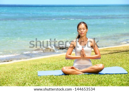 Yoga woman meditating woman relaxing by ocean sea doing the Sukhasana, easy pose. Woman in meditation in beautiful ocean landscape retreat. Meditation, yoga and relaxation concept. - stock photo