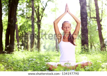yoga woman on green grass in forest