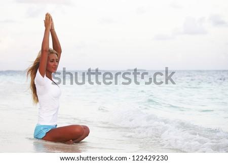 yoga woman on sea coast - stock photo