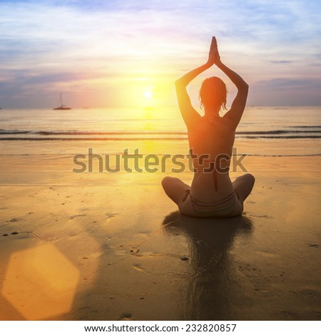 Yoga woman on the beach at amazing sunset.
