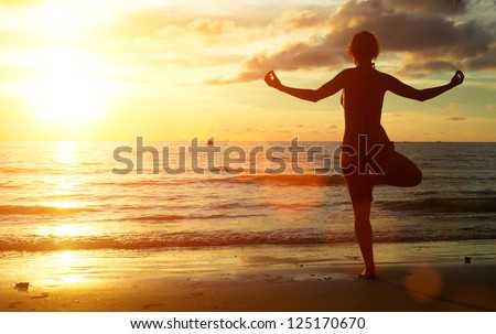 Yoga woman on the beach during sunset. - stock photo