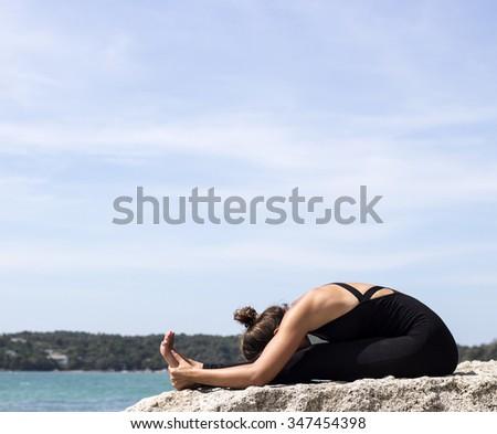 Yoga woman poses on beach near sea and rocks. Phuket island, Thailand - stock photo
