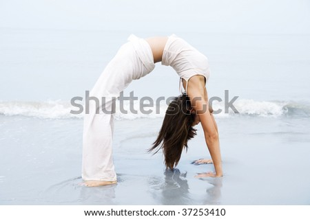 Yoga. Woman practicing Bridge Position Yoga on the beach.