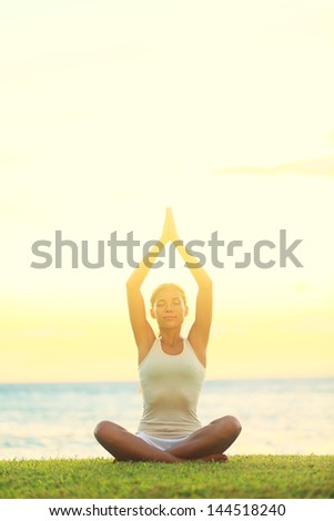Yoga woman relaxing by sea at sunrise or sunset doing the Sukhasana, easy pose facing water. Woman meditating in beautiful ocean landscape retreat. Meditation, yoga and relaxation concept. - stock photo