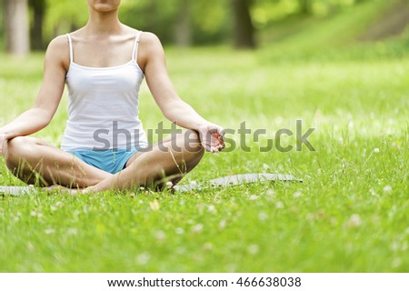 Yoga woman siting on grass meditating in lotus position.