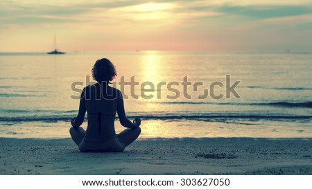 Yoga woman sitting in lotus pose on the beach during amazing sunset.