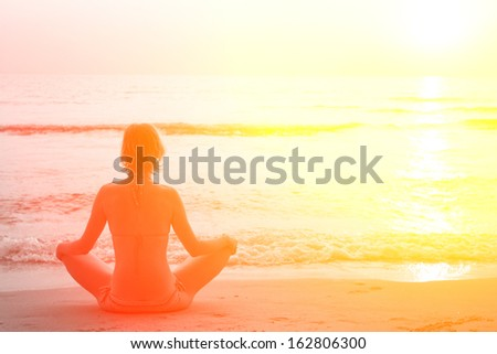 Yoga woman sitting in lotus pose on the beach during sunset, in bright colors. - stock photo