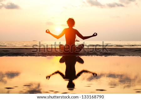 Yoga woman sitting in lotus pose on the beach during sunset in bright colors. (with reflection in water) - stock photo