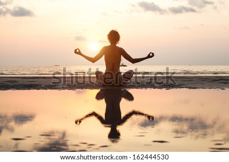 Yoga woman sitting in lotus pose on the beach during sunset, in bright colors, with reflection in water. - stock photo