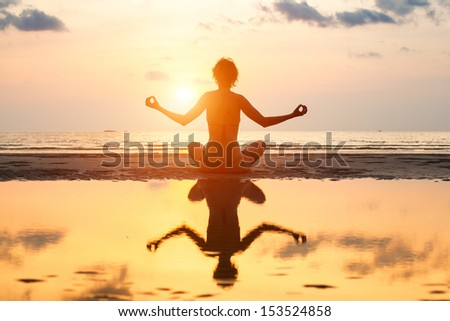 Yoga woman sitting in lotus pose on the beach during sunset, with reflection in water. - stock photo