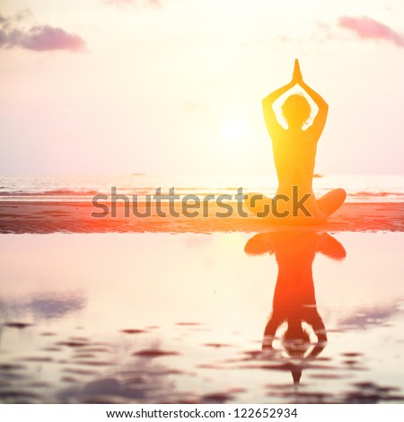 Yoga woman sitting in lotus pose on the beach during sunset, with reflection in water (bright colors) - stock photo