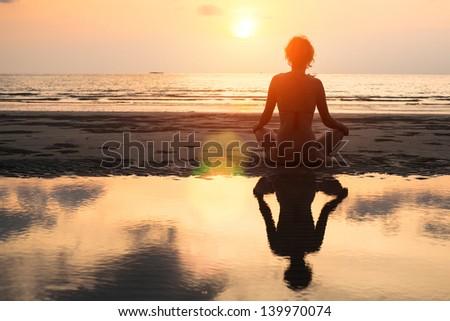 Yoga woman sitting in lotus pose on the beach during sunset, with reflection in water - in bright colors. - stock photo