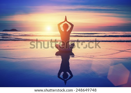 Yoga woman sitting in lotus pose on the beach with reflection in water during sunset. - stock photo