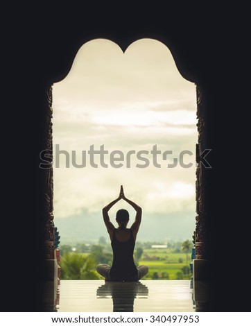 Yoga woman sitting in lotus pose on the temple during sunrise, with reflection in floor - vintage style color effect