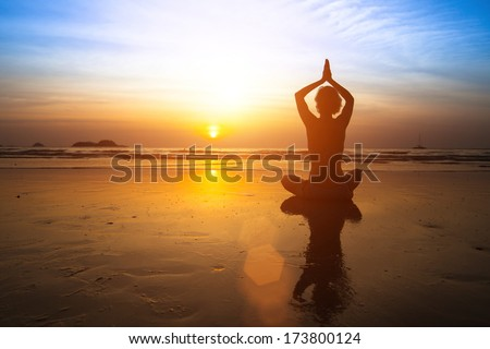 Yoga woman sitting on sea coast at sunset.