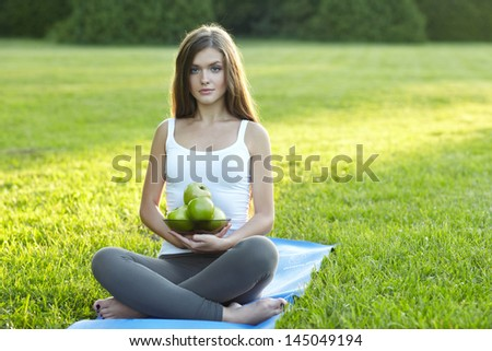 yoga woman with apples on green grass. Outdoor - stock photo