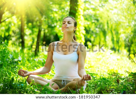 Yoga. Young Woman doing Yoga Exercises Outdoor. Beautiful Girl practicing yoga in the park