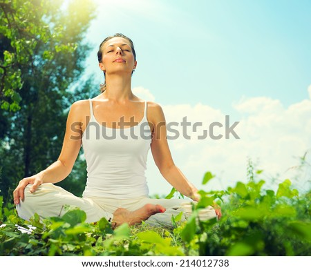Yoga. Young Woman doing Yoga Exercises Outdoors. Beauty girl relaxing outdoor. Healthy lifestyle concept