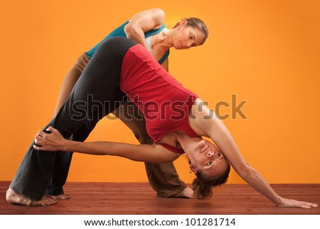 Yogasana instructor with student stretching over orange background
