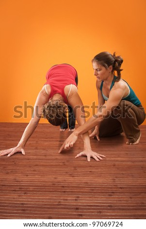 Yogasana teacher assisting her student with the Adho Mukha Svanasana posture - stock photo