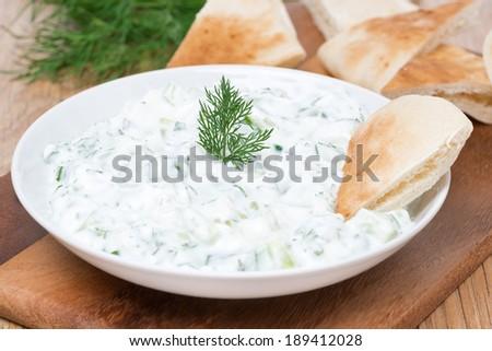 yoghurt sauce tzatziki with herbs, cucumber and garlic and pita bread, close-up, horizontal - stock photo