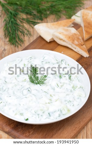 yoghurt sauce tzatziki with herbs, cucumber and garlic, vertical, top view - stock photo