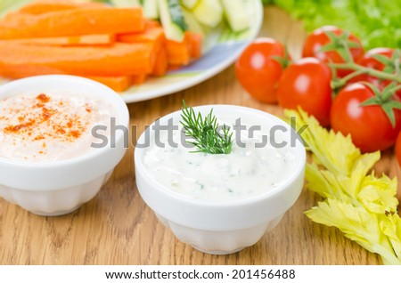 yoghurt sauce with herbs, sauce with sun-dried tomatoes and paprika to assorted fresh vegetables on a wooden table close-up