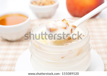 yoghurt with honey, fresh peaches, nuts in a spoon, close-up - stock photo