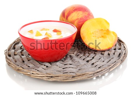 Yoghurt with peach in bowl on wicker mat isolated on white