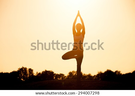 Yogi girl in asana pose. Silhouette of woman practicing yoga pose standing in the lotus position with her hands raised against a colorful sunset sky. - stock photo