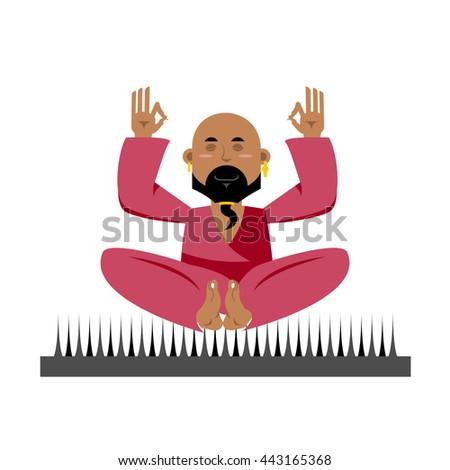 Yogi on nails. Indian yogi sits on spike. nirvana Meditation. Man practicing yoga exercises. Bald man with beard meditates - stock photo